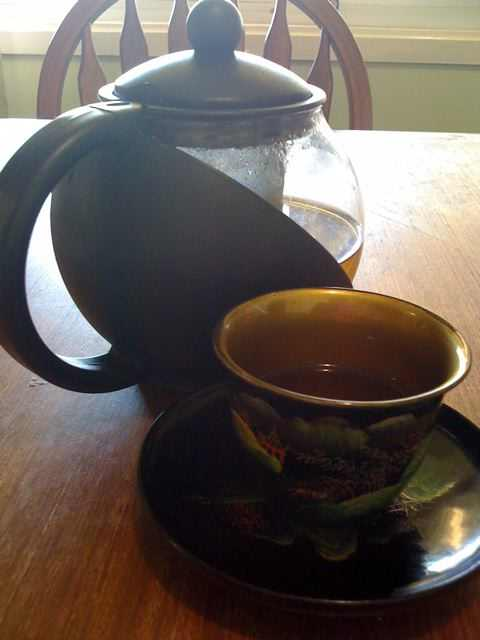 Chinese tea cup and pot with herbal tea.
